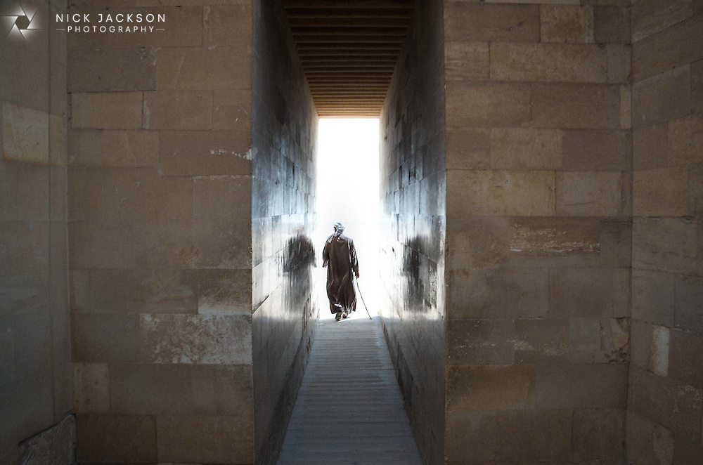As an Egyptian Priest heads towards the bright lights of the exit of an ancient temple, his reflection is caught in the smooth sides of the walls