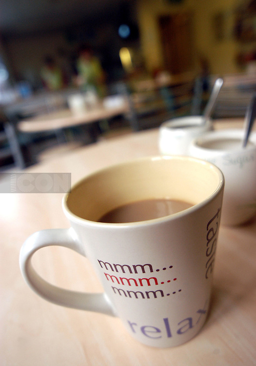 STOCK mug of coffee on a table in a cafe. The mug has a selection of words on it....