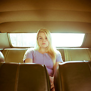 A 17-year-old Caucasian blond-haired girl sits in the back seat of a 1972 Dodge Polara in Cortland, NY.