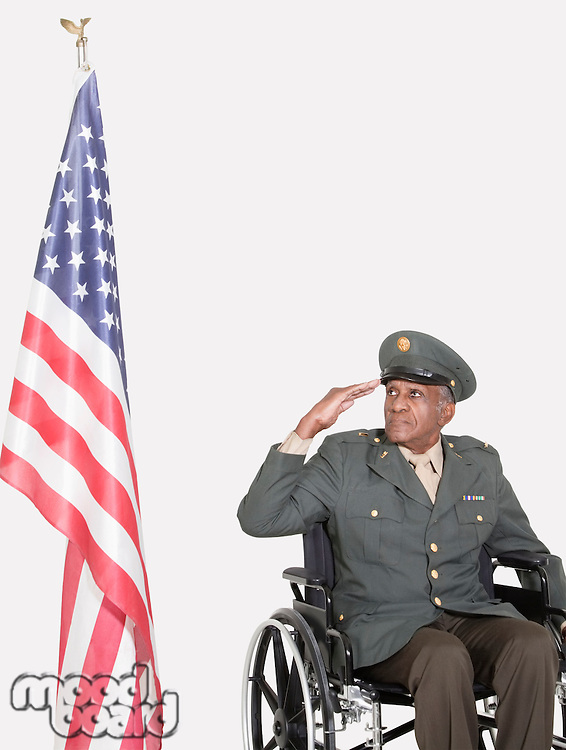 Senior male US military officer in wheelchair saluting American flag over gray background