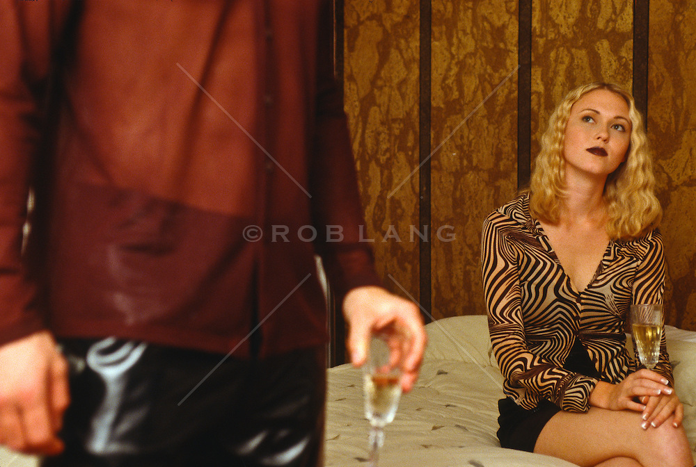Woman seated on a bed holding a glass of champagne and detail of a man holding a glass of champagne