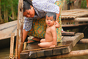 A mother bathes her child on Inlé Lake, Burma (Myanmar). Her house, like most in the area, is built on stilts and sits directly on top of the lake (not along the shore)