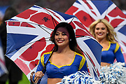 An LA Rams cheerleader smiles as she carries a Union Jack umberella during the International Series match between Los Angeles Rams and Cincinnati Bengals at Wembley Stadium, London, England on 27 October 2019.