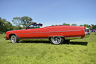 Old Westbury, New York, United States. 7th June 2015. A red 1975 Pontiac Grand Ville convertible, seen from driver side, side, is shown at the 50th Annual Spring Meet Car Show sponsored by Greater New York Region Antique Automobile Club of America. Over 1,000 antique, classic, and custom cars participated at the popular Long Island vintage car show held at historic Old Westbury Gardens.