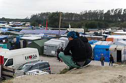 October 16, 2016 - Calais, France - Migrants sit in the Calais Jungle on a Sandhill, in Calais, France, on October 16, 2016. The refugee camp on the coast to the English Channel is to be cleared in the next few days, according to the French government. In the camp live around the 1000 refugees and wait for the possibility to travel further through the Eurotunnel to the UK. (Credit Image: © Markus Heine/NurPhoto via ZUMA Press)