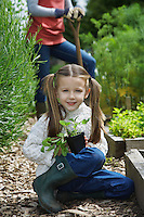 Girl (5-6) in garden with mother portrait