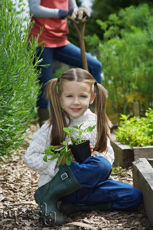 Girl (5-6) in garden with mother portrait