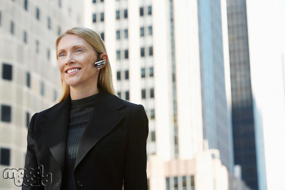 Businesswoman using wireless headset outdoors