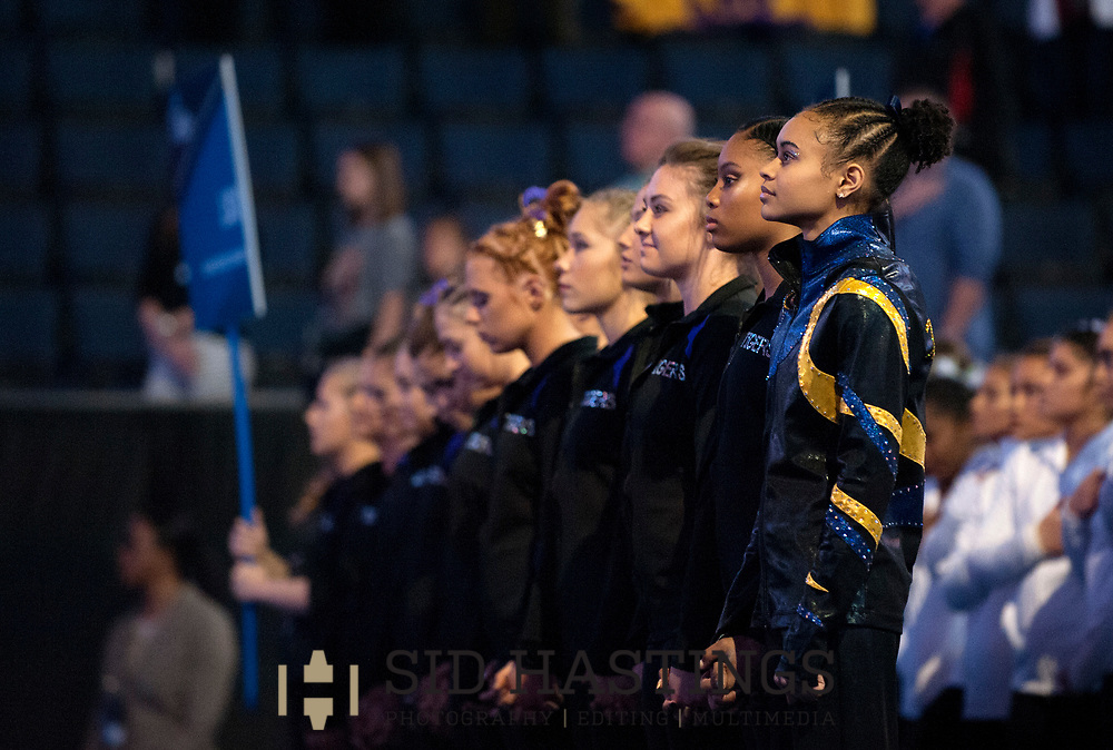 20 APRIL 2018 -- ST. LOUIS -- Michigan gymnast Brianna Brown (right) joins members of the LSU gymnastics team during the playing of the National Anthem before 2018 NCAA Women's Gymnastics Championship Semifinals in St. Louis Friday, April 20, 2018. Brown, an individual competitor, worked with the Tigers on Friday. LSU finished second in the semifinal, joining UCLA and Nebraska in advancing from the first semifinal into the Super Six championship round on Saturday.<br /> <br /> Photo &copy; copyright 2018 Sid Hastings.
