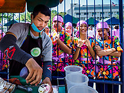 29 OCTOBER 2018 - PHRA PRADAENG, SAMUT PRAKAN, THAILAND: An ice cream vendor serves coconut ice cream to school children dressed for a parade for the long boat races in Phra Pradaeng. The longboat races go about one kilometer down the Chao Phraya River to the main pier in Phra Pradaeng. The boats are crewed by about 20 oarsmen. Longboat racing traditionally marks the end of the Buddhist Rains Retreat (called Buddhist Lent) in Thai riverside communities.        PHOTO BY JACK KURTZ