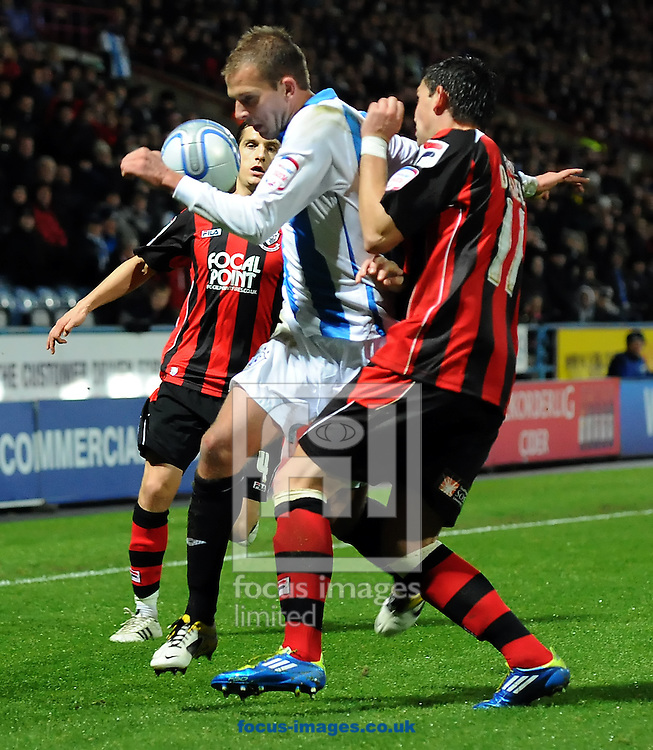 Picture by Graham Crowther/Focus Images Ltd. 07763140036.10/12/11 .Jordan Rhodes of Huddersfield is stopped by the combined efforts of Shaun Cooper & Charlie Daniels of Bournemouth during the Npower League 1 game at the Galpharm Stadium, .