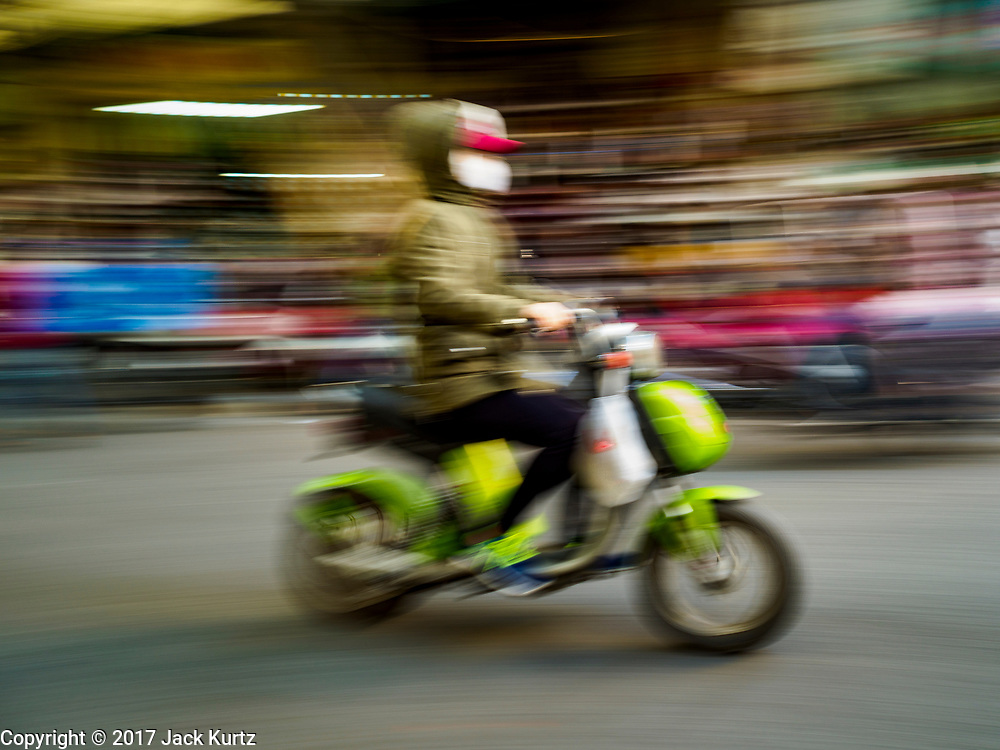 """21 DECEMBER 2017 - HANOI, VIETNAM:  Motorcycle traffic in the old quarter of Hanoi. The old quarter is the heart of Hanoi, with narrow streets and lots of small shops but it's being """"gentrified"""" because of tourism and some of the shops are being turned into hotels and cafes for tourists and wealthy Vietnamese.  PHOTO BY JACK KURTZ"""