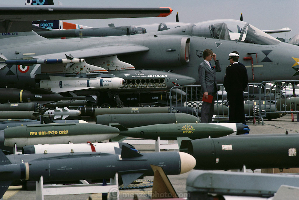 A salesman and potential military buyers surrounded by jet fighters and missiles at the Paris Air Show, at Le Bourget Airport, France. Held every other year, the event is one of the world's biggest international trade fairs for the aerospace business.
