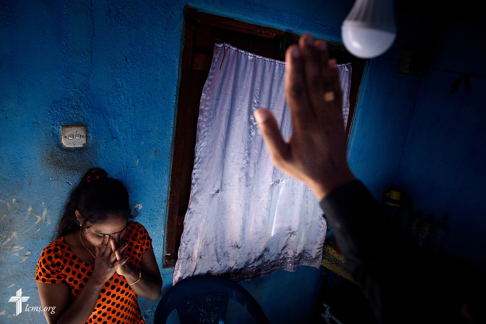 A woman prays with the Rev. P. Gnanakumar, and the Rev. Steven Mahlburg, LCMS career missionary to Sri Lanka (both not pictured), during a home visitation on Saturday, Jan. 20, 2018, on the Eila rubber plantation in the Sabaragamuwa Province of Sri Lanka. LCMS Communications/ Erik M. Lunsford
