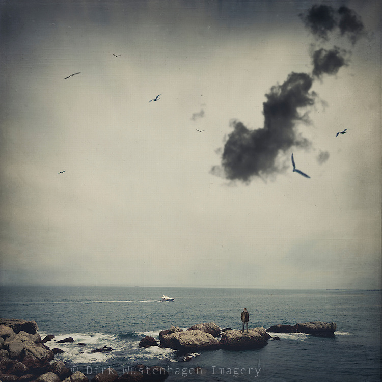 Man standing on rocks in the ocean with a boat passing by - manipulated and texturized photograph