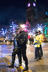 © Licensed to London News Pictures . 31/12/2017. Manchester, UK. Armed police patrol Albert Square as thousands gather to watch as Manchester celebrates the start of 2018 , with a fireworks display in front of the Town Hall in Albert Square . This year's celebration sees additional security, including concrete barriers around the square and bag searches and the event includes a poetry reading by Tony Walsh , in memory of those who were killed at a terrorist attack after at the Manchester Arena in May 2017. Photo credit: Joel Goodman/LNP