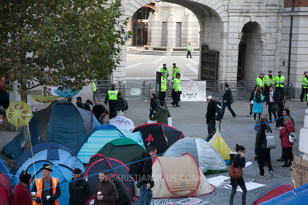 The view into Pator Noster Square and the stock exchange - heavily police protected. Camping activists slowly waking up under a giant tarpaulin beside the main entrance to the cathedral. Day three of the occupation - and the first Monday.  The Occupy London Stock Exchange movement was formed in London in solidarity with the US based Occupy Wall Street. The movements are a respons and in anger to what is seen by many as corporate greed and a failed banking system being bailed out by the public, - which in return are suffering austerity measures to make up for the billions of lost money. The movement occupied the St Paul's Square in the City of London Sat Oct 15 after it failed to secure and occupy Pator Noster Square and the Stock Exchnage itself.