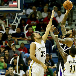 Mar 7, 2016; New Orleans, LA, USA; Sacramento Kings center DeMarcus Cousins (15) shoots over New Orleans Pelicans forward Ryan Anderson (33) and guard Jrue Holiday (11) during the second half of a game at the Smoothie King Center. The Pelicans defeated the Kings 115-112. Mandatory Credit: Derick E. Hingle-USA TODAY Sports