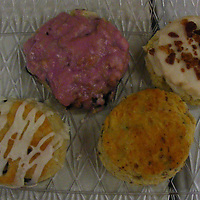 Clockwise is a platter of blueberry, maple bacon, sausage cheddar and chocolate chip biscuits.