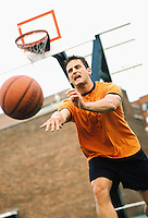 Mid 20's Caucasian Man playing pick-up basketball, passing the ball up court.<br />