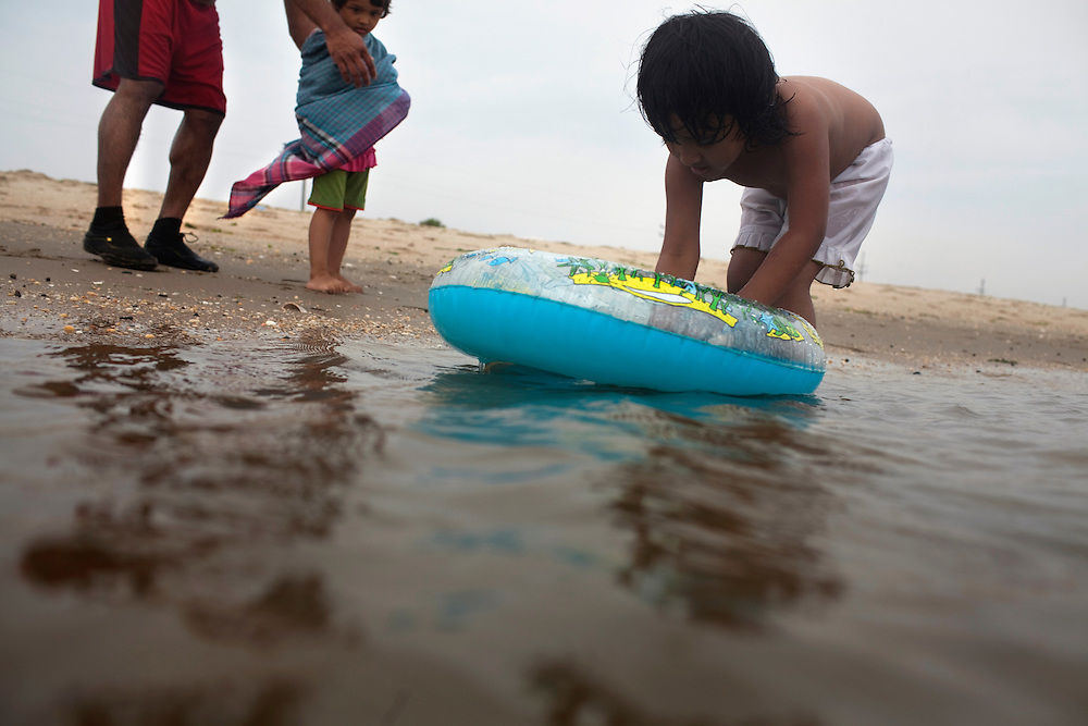 Sandy Hook, NJ - June 30, 2013 :  Raika Meah, 3, right, plays in the water watched by her sister Ramisa Meah, 2, while Imran Habib keeps her warm on the beach of Sandy Hook, NJ on June 30, 2013. People are returning to the New Jersey beaches for the summer after recovery efforts post Sandy.