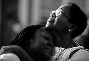 "Overcome by grief, Clarissa Jackson, left, is comforted by her friend Gillettie Bennett, right, as they visit the makeshift memorial on the sidewalk in front of Mother Emanuel on June 21, 2015. In Charleston, the church is affectionately known as ""Mother Emanuel,"" as a nod to its age and its eminence in the community."
