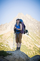 Woman with heavy backpack on posing before Mount Stuart in the Central Cascades of Washington State, USA.