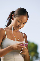 Young Woman Adjusting MP3 Player