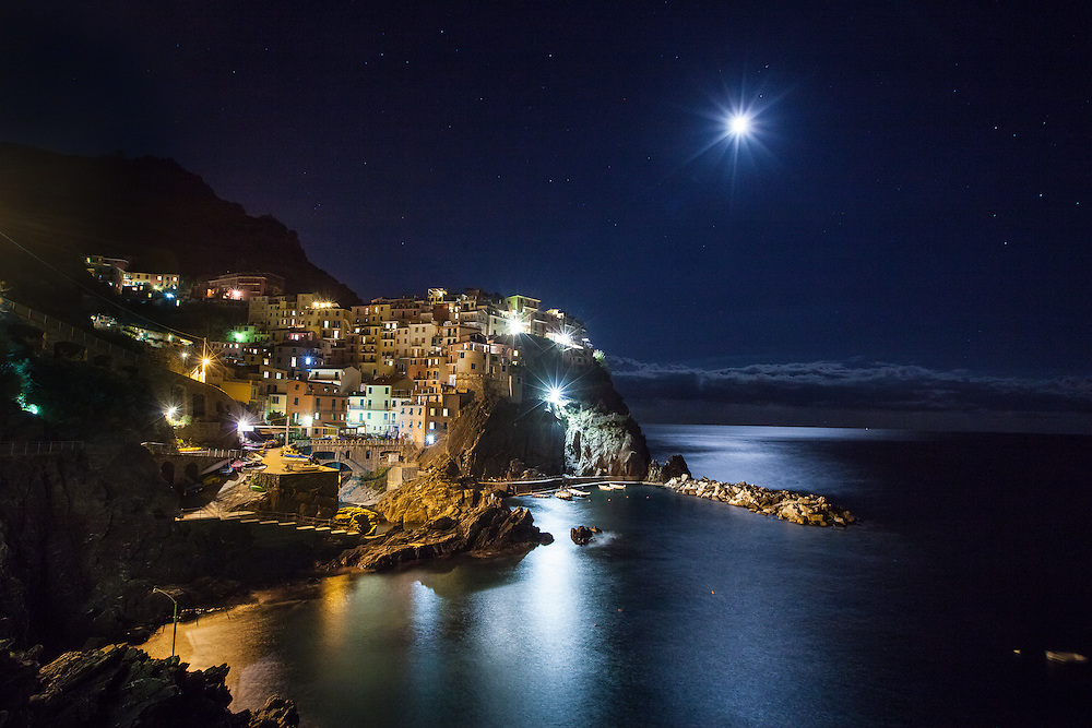 Photo of Manarola on the Cinque Terre by moonlight over the Mediterranean.