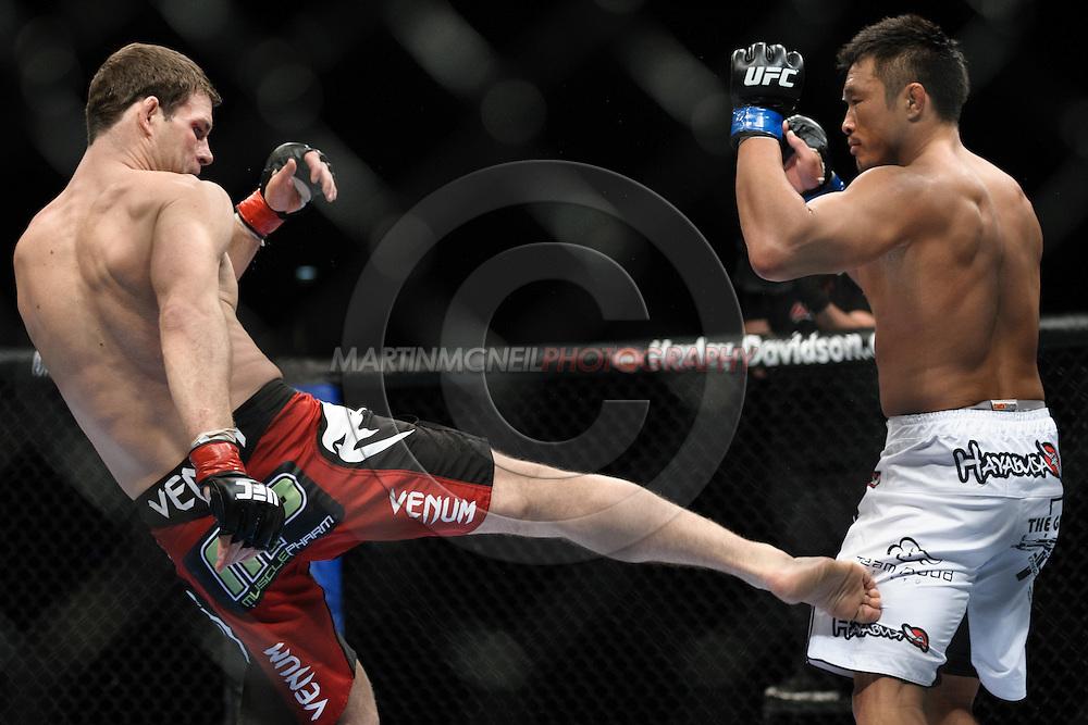 """LONDON, ENGLAND, OCTOBER 2010: Michael Bisping (left) kicks the leg of Yoshihiro Akiyama during """"UFC 120: Bisping vs. Akiyama"""" inside the O2 Arena in Greenwich, London"""