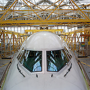 During a lull in activity, a Boeing 747 is swathed in engineering gantries during a major check (maintenance schedule) at the British Airways Heathrow base in London England. As if in a hospital ER several metres off the ground, yellow struts surround the aircraft's forward nose section and the first class windows along the white fuselage allowing mechanics, engineers and avionics specialists unimpeded access to every element of the air frame. Neon tubes illuminate the hangar that houses airliners, serviced here between transcontinental commercial passenger flights.