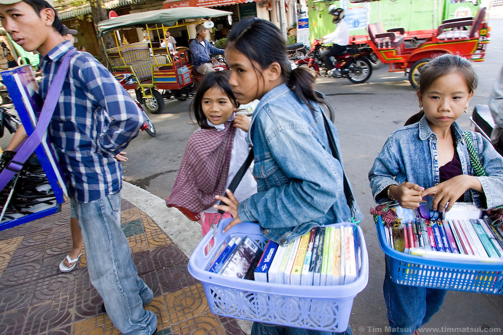 Children work the tourists on the Tonle Sap riverfront in downtown Phnom Penh, Cambodia.  At first many will say they sell books for a month to earn enough money to pay for a month of public school but later many reveal it is often their parents they work for, selling cheap and illegal reprints likely to interest tourists such as books on local history and travel guides by Lonely Planet. They average two to three books per day, grossing about $6 dollars.