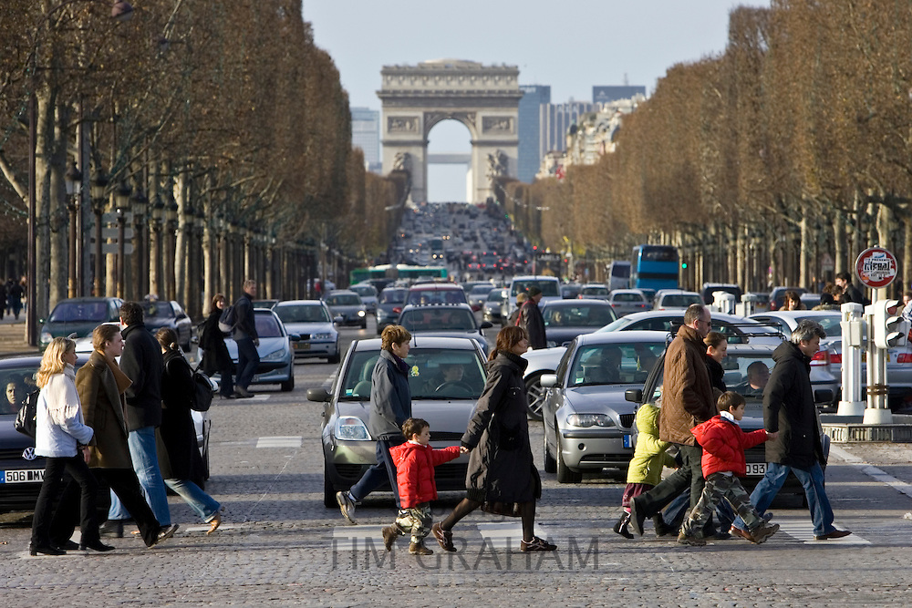 Traffic stops for pedestrians on zebra crossing across Champs-Élysées in front of the Arc de Triomphe, Central Paris, France