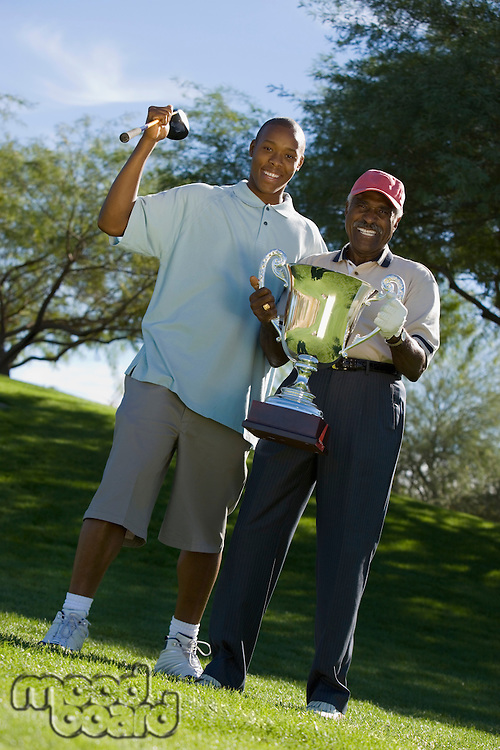 Grandfather and Grandson Holding Golf Trophy