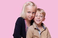 Portrait of young girl with happy brother over pink background