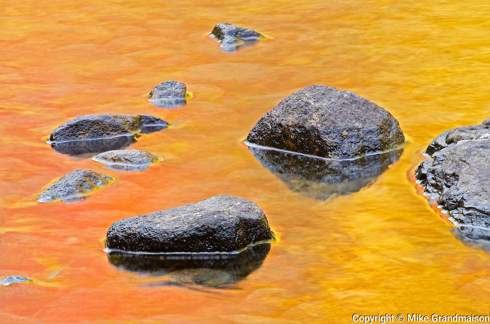 Rocks in Dryberry Creek with autumn colored reflections of trees<br /> Sioux Narrows<br /> Ontario<br /> Canada