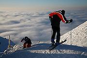 Deux générations sur les skis: grand-père avec son filleul sur les skis, profitant d'une journée de soleil sur le Moléson avc mer de brouillard en dessous. Skifahrer auf dem Moléson, bereit zur Abfahrt. © Romano P. Riedo