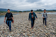 Men walk along the stone beach of Manhenuan village, Xishuangbanna, China.