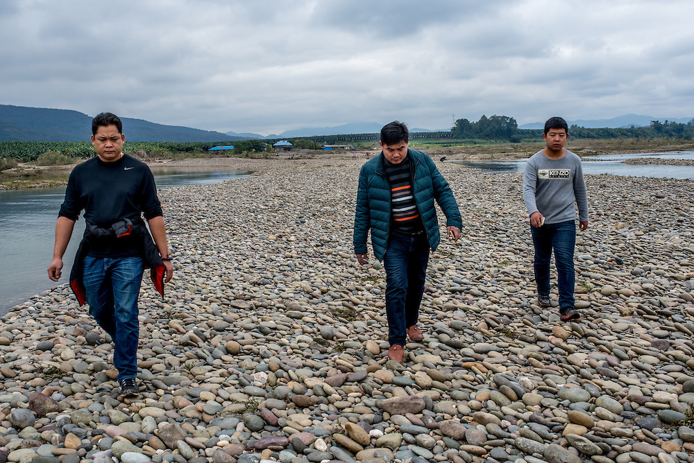 Men walk along the stone beach of Manhenuan village, Xishuangbanna, China.