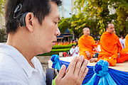 20 OCTOBER 2012 - BANGKOK, THAILAND:  A man bows his head in prayer before making a donation to a Buddhist monk during an alms giving ceremony in Bangkok. More than 2,600 Buddhist Monks from across Bangkok and thousands of devout Thai Buddhists attended the mass alms giving ceremony in Benjasiri Park in Bangkok Saturday morning. The ceremony was to raise food and cash donations for Buddhist temples in Thailand's violence plagued southern provinces. Because of an ongoing long running insurgency by Muslim separatists many Buddhist monks in Pattani, Narathiwat and Yala, Thailand's three Muslim majority provinces, can't leave their temples without military escorts. Monks have been targeted by Muslim extremists because, in the view of the extremists, they represent the Thai state.       PHOTO BY JACK KURTZ