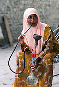 Woman smoking tobacco in a water pipe. The island of Utheem. North Maldives.