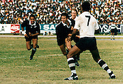 Wayne Smith looks to pass against Fiji, Suva, 1984. Other All Blacks pictured are Steve Pokere and Andy Donald. NZ 45, Fiji 0. Photo: PHOTOSPORT/Peter Bush