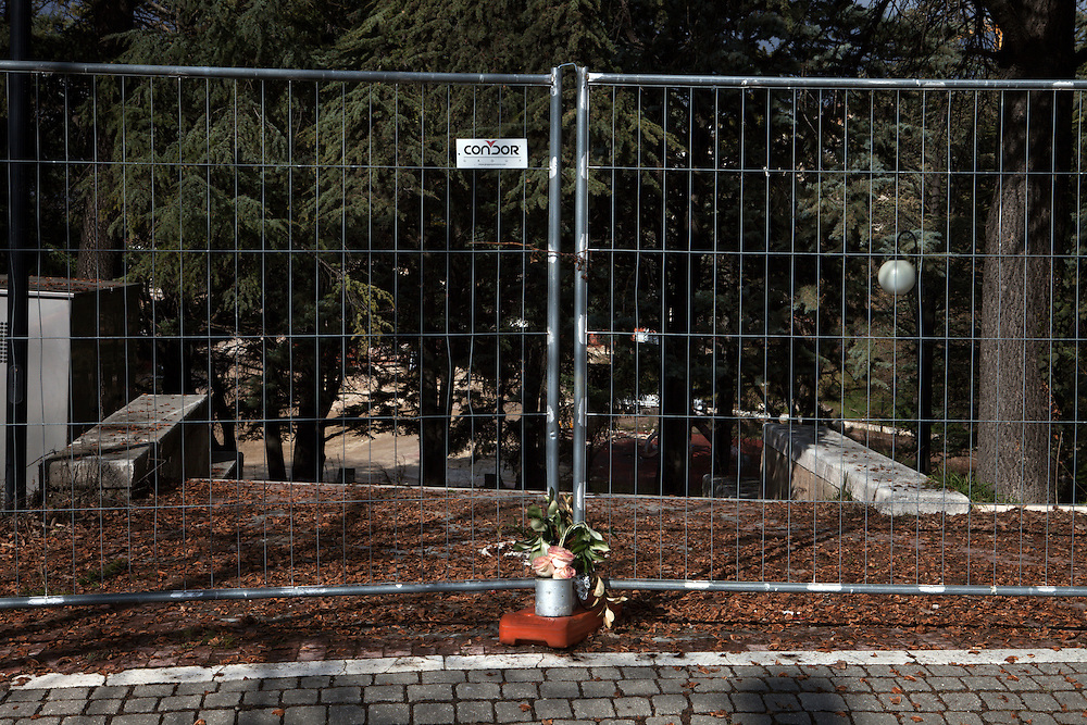 Flowers put on an eclosure of a dangerous area for memory of victims of the earthquake in the neighborhood called Villa where 200 people died . On 6 April 2009 a strong earthquake hit the city of L'Aquila, in the central Abruzzo region of Italy, leaving 308 dead and tens of thousand homeless. 4  years after In the historical center of the city few signs of reconstructions could be seen. On the other hand the effects of the of abandonment add up to the destruction of the quake.