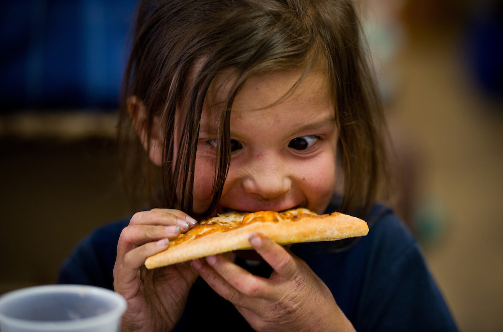 """Xavier Mascareñas/Treasure Coast Newspapers; Savannah Beach, a Port St. Lucie 5-year-old who attends Redeemer Lutheran School with her 10-year-old brother Cameron, dedicates her full attention to taking a bite of cheese pizza prepared in the Little Caesars Love Kitchen during its stop at Redeemer Lutheran Church in Stuart on April 9, 2015. Jerry Felton, coordinator at the church's soup kitchen named His Servants' Place, said """"it's quite a special treat,"""" adding that the only other times they serve pizza are on special occasions."""