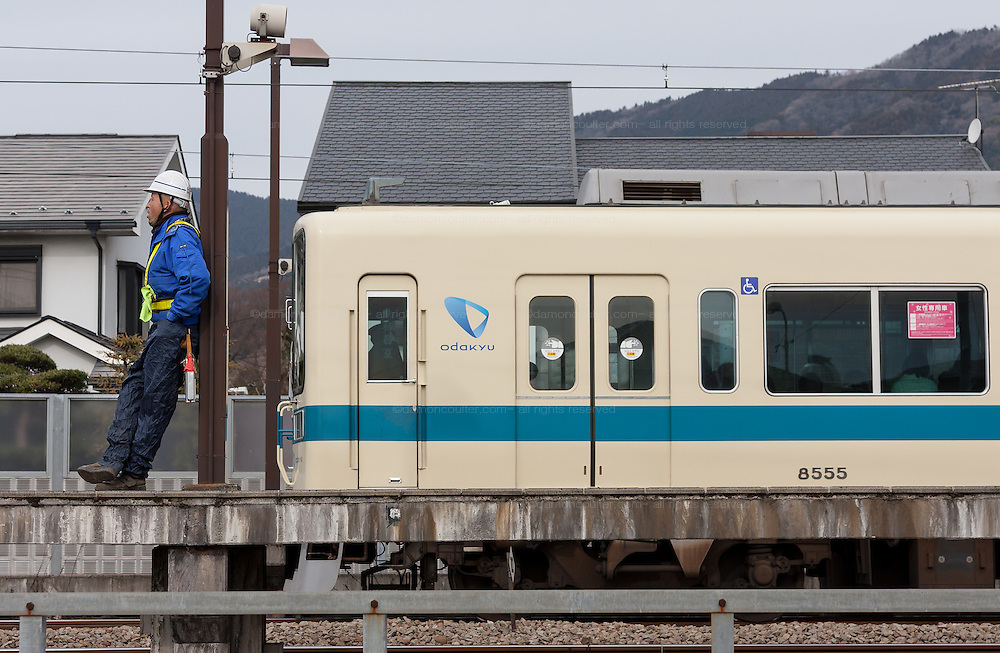 A workman rests near an Odaku Line train at Shin Matsuda station. Kanagawa, Japan. Saturday January 15th  2011