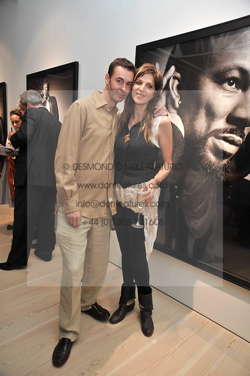 MARTHA FIENNES and her husband GEORGE TIFFIN at an exhibition of photographic portraits by Bryan Adams entitled 'Hear The World' at The Saatchi Gallery, King's Road, London on 21st July 2009.