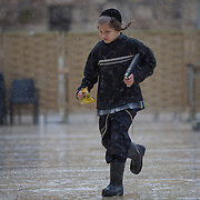 A young ultra-orthodox boy runs on the plaza as snow and rain fall at The Western Wall on January 7, 2015 in Jerusalem, Israel. (Photo by Elan Kawesch)