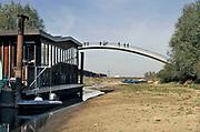Nederland, the netherlands, Nijmegen, 19-10-2018 Binnenvaartschepen varen in de Waal langs de drooggevallen oever . Door de aanhoudende droogte staat het water in de rijn, ijssel en waal extreem laag . Laagterecord en de laagste officiele stand ooit bij Lobith gemeten . Schepen moeten minder lading innemen om niet te diep te komen . Hierdoor is het drukker in de smallere vaargeul . Door te weinig regenval in het stroomgebied van de rijn is het record verbroken . Woonboot in een strang ligt op de bodem. Op de achtergrond vaart een schip in de rivier.Foto: Flip Franssen