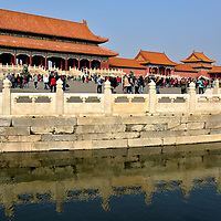 Description of Forbidden City in Beijing, China<br /> Forbidden City is the must see attraction in Beijing. Constructed in the early 15th century, this former home to 24 emperors showcases almost 1,000 exquisite examples of Chinese palatial architecture. From 1420 until 1912, you could not enter the property without permission from the emperor. But after the end of the Qing dynasty, the 180 acre complex opened in 1925 as the Palace Museum. Now this UNESCO World Heritage Site welcomes about 16 million visitors a year, making it the world&rsquo;s number one tourist attraction. One beautiful example of why Forbidden City is so popular is this view of the Gate of Supreme Harmony with marble balustrades reflecting on Inner Golden Water River. On the right are the Gate of Manifest Virtue (Zhaode men) and the Lofty Pavilion (Chong lou).