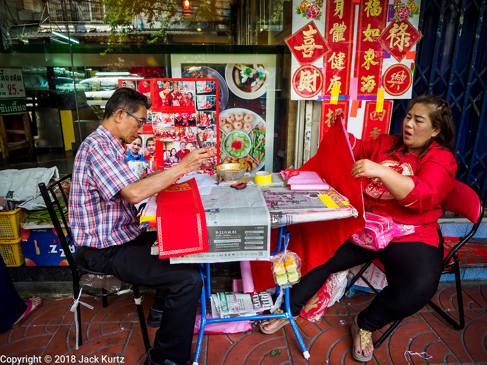 07 FEBRUARY 2018 - BANGKOK, THAILAND:  A traditional Chinese calligrapher in Bangkok's Chinatown makes New Year's banners that are hung in people's homes or given as gifts. The Lunar New Year, also called Tet or Chinese New Year, is 16 February this year. The coming year will be the Year of the Dog. Thailand has a large Chinese community and Lunar New Year is widely celebrated in Thailand, especially in Bangkok and large cities with significant Chinese communities.     PHOTO BY JACK KURTZ